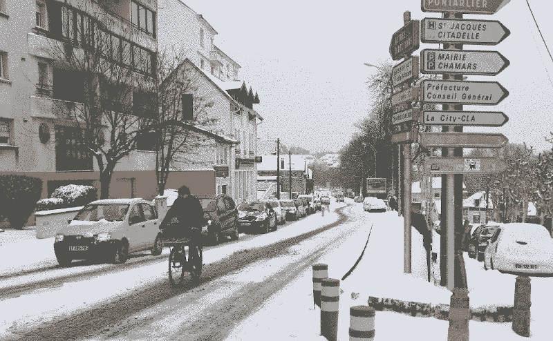 Cycliste bisontin dépassant une file de voiture par temps de neige